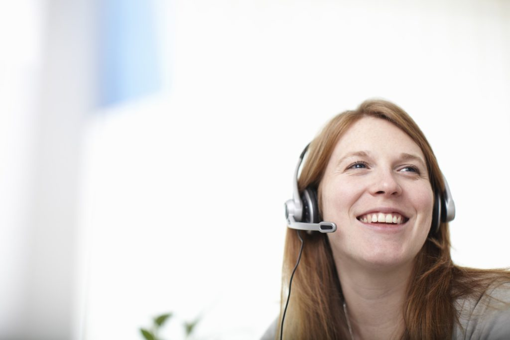 Happy girl with headset next to computer