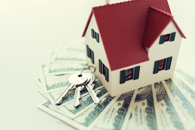 close up model of a home and money